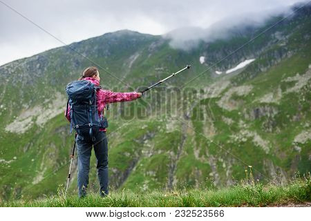 Rear View Shot Of A Female Backpacker Standing On Top Of A Hill Pointing Away With Her Trekking Pole