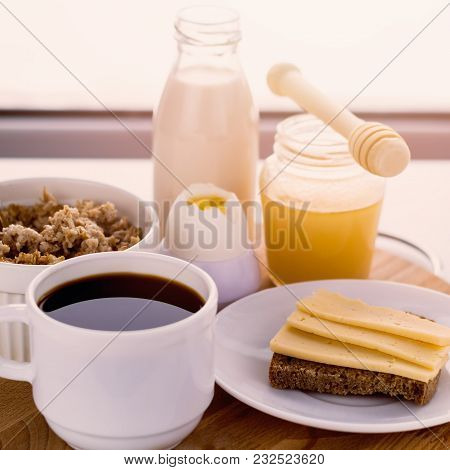 Healthy Breakfast Fresh Cereal, Cheese Sandwich, Hard Boiled Egg, Milk Bottle, Coffee Cup And Honey