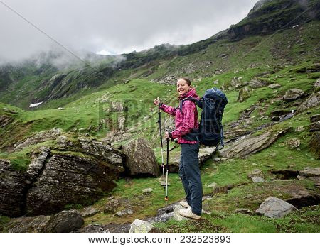 Happy Female Tourist Shows Gesture With Finger Class At Hiking In The Valley Of The Romanian Mountai