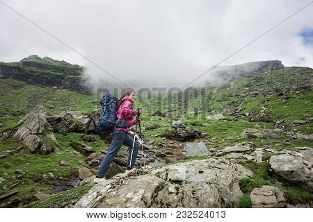 Low Angle Shot Of A Female Hiker Walking In The Mountains With A Backpack And Trekking Poles Copyspa