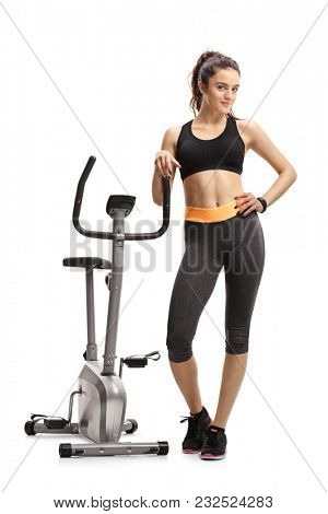Full length portrait of a fitness woman leaning on a stationary bike isolated on white background