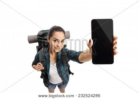 Female teenage tourist showing a phone isolated on white background