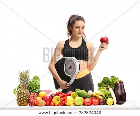 Fitness woman with a weight scale and an apple behind a table with fruit and vegetables isolated on white background