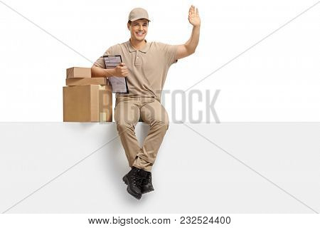 Delivery guy with packages and a clipboard sitting on a panel and waving at the camera isolated on white background