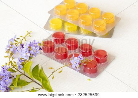 Cough Sore Throat Pastille And Purple Flowers On Background White