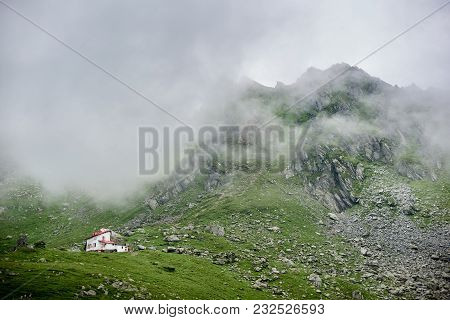 Fog Descends To The Mountains In The Valley Of The Fagaras Mountains. Lonely House In The Valley At