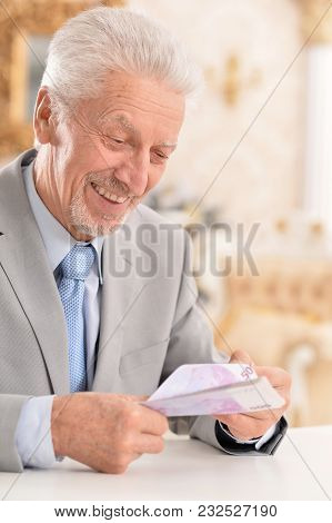 Portrait Of Senior Man With Paper Plane Made Of Money Bill