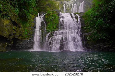 A Small Waterfal With Beautiful Scenery Of Lush Rocks And Forest Line