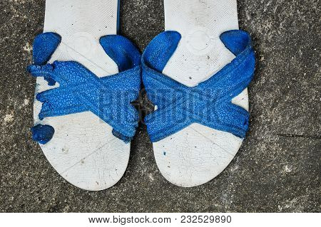 Old Unused Rubber Sandal With Tear And Torn On The Outdoor Concrete Floor.