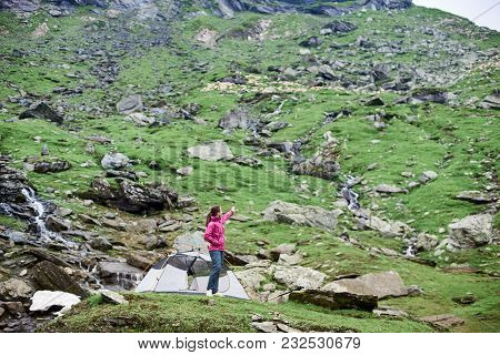 Woman Hiker Standing Near Her Tent In Mountain Valley Pointing Away Copyspace Explorer Exploring Tra
