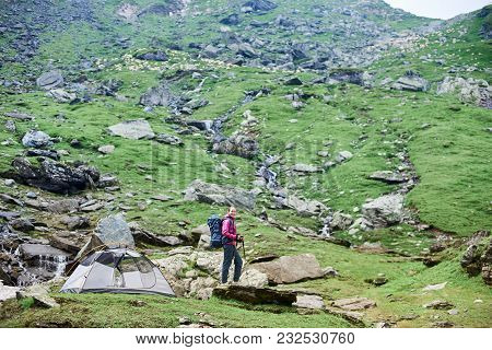 Shot Of A Woman Hiker With A Backpack And Trekking Poles Standing Near Her Tent In The Mountains Val
