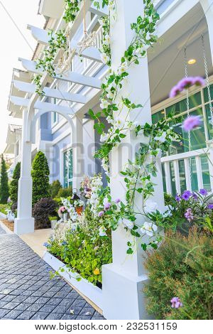 An Artificial Ivy With White Flowers Around The Pillar With Front Yard Background.