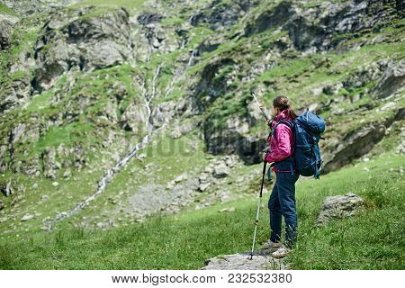 Young Woman Backpacker With Trekking Sticks And A Backpack Is Standing On A Stone At The Foot Of The