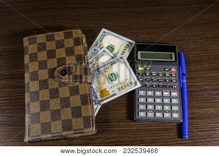 Notebook With Dollars, Pen And Calculator On Office Desk