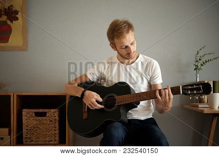 Handsome Young Man Practicing Guitar Play At Home