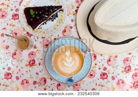 A Cup Of Latte, Cappuccino Or Espresso Coffee With Milk With Blueberry Cheesecake Pie And Hat On Flo
