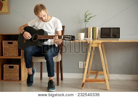 Young Musician Playing Acoustic Guitar In His Apartment