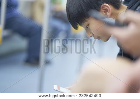 Asian Teenage Boy Using Smart Phone On The Mrt