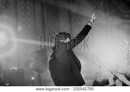Singer With A Microphone On The Stage Raised One Hand With A Bright Light