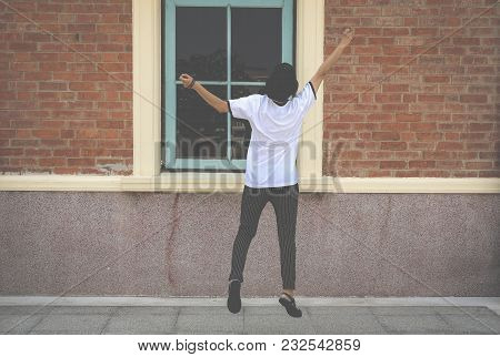 Backside Of Woman Jumping With Happiness Outdoors.