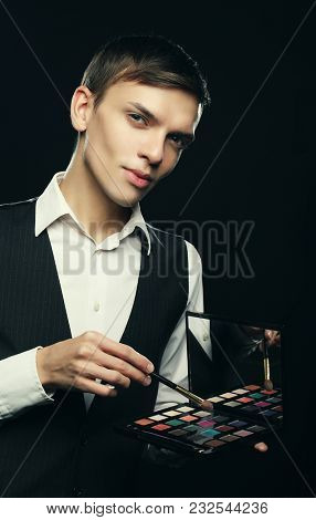 Male make-up artist staying on dark background, holding professional brush and shadows palette, looking at camera, suggesting to do make up for you.