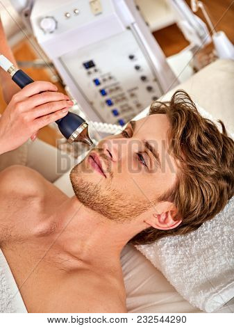 Ultrasonic facial treatment on ultrasound face machine. Man has electric lift massage spa salon. Stimulation male muscles. Professional microcurrent therapy. Improvement of skin condition.