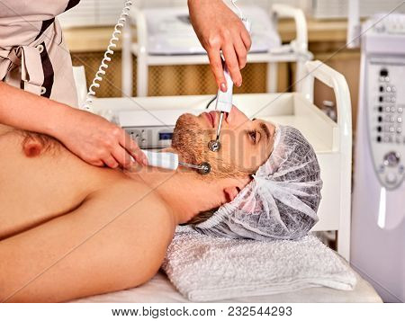 Facial massage at beauty salon. Electric stimulation skin care of man. Equipment for microcurrent lift face. Anti aging face and neck and close up rejuvenation. Acne Removal. poster