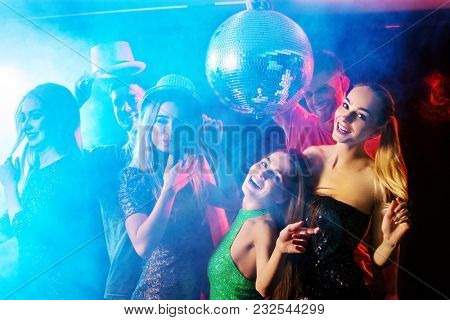 Dance party with group people dancing. Women and men have fun in night club. Rest after hard day at work. Back light on girls hair. People in brilliant suits dance under influence of alcohol.