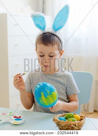 Child Paints Eggs On Wooden Workpiece Eggs Sitting At Table In A White Room