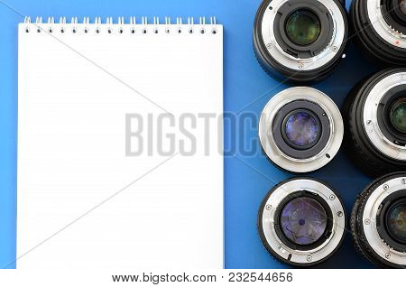 Several Photographic Lenses And White Notebook Lie On A Bright Blue Background. Space For Text