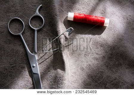 Scissors And Reel Of Red Thread On Gray Fabric
