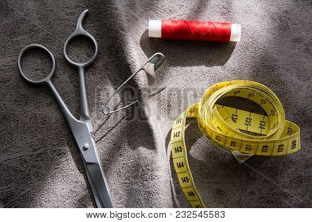 Measuring Tape, Scissors And Reel Of Red Thread On Gray Fabric