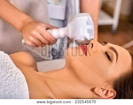 Ultrasonic facial treatment ultrasound face machine. Woman receiving electric lift massage spa salon. Electronic stimulation female muscles. Improvement of skin condition.