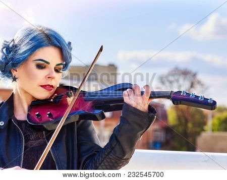 Woman perform music on violin in park outdoor. Girl performing jazz on city street. Spring outside with blue hairstyle background. Good hobbies for people.