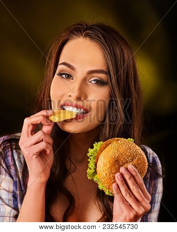 Woman eating piece of cheese and hamburger. Portrait of student consume fast food on table. Girl trying to eat junk. Advertise fast food on daek background. Snack to alcoholic beverages.