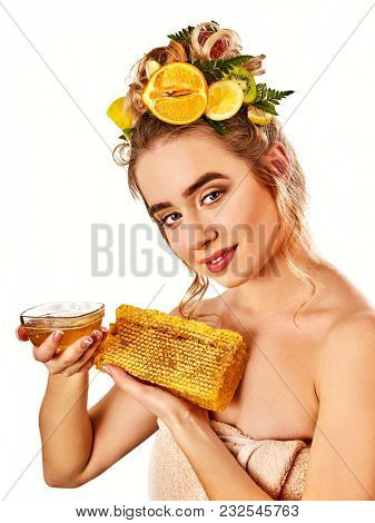 Honey facial mask with fresh fruits for hair and skin on woman head. Girl with beautiful face hold honeycombs for homemade organic skin and hair therapy. Improvement of skin condition.