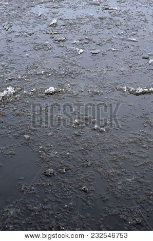 Damaged Asphalt Road With Potholes, Filled With Water With Ice, Caused By Freezing And Thawing In Wi
