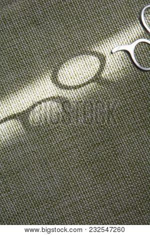 Shadow Of Scissors On Green Fabric