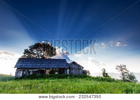 Fantastic evening sun beams in the countryside and the old hut. Location rural place of Ukraine, Europe. Scenic image of gorgeous nature landscape, attractive mountain view. Beauty of earth.