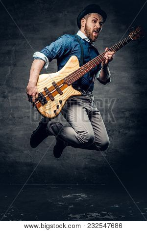 Funny Bass Player In A Jump Dressed In A Cylinder Hat.