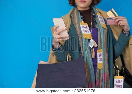 Asian Shopaholic Woman In Clothes With Sale Price Tags Using Application On Her Smartphone
