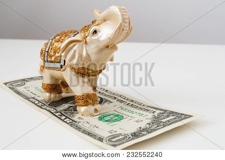 One Dollar And An Elephant Figure On White Background