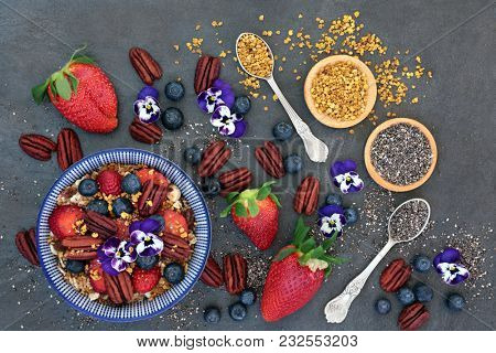 Healthy breakfast super food concept with granola, viola flowers, pollen grain, fresh berry fruit, nuts and chia seeds,   high in protein, omega 3, anthocyanins, antioxidants, protein and vitamins.