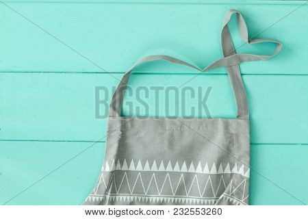 Apron Kitchen For Cooking A Gray Color Lies On The Table, The Heart Of The Strings. Love Of Cooking