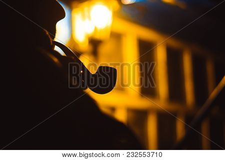 Man Smoking Pipe At Night In The Light Of A Lantern