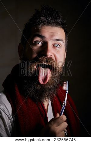 Young Handsome Bearded Man Portrait With Long Beard And Moustache Showing Tongue On Grimace Face. Be