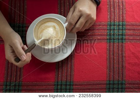 Coffee Background Concept. Hand Holding A Latte Cup And Spoon On Red Tablecloth With Free Copy Space