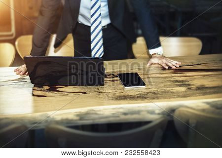 Business And Technology Concept. Businessman Put Hands On Table With Mobile And Tablet Computer. Pic
