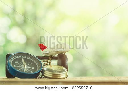 Travel Background Concept. Small Airplane With Gold Watch And Compass On Wood Table With Blurred Tre