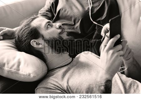 Cute couple on a couch sharing smartphone love, internet and music concept